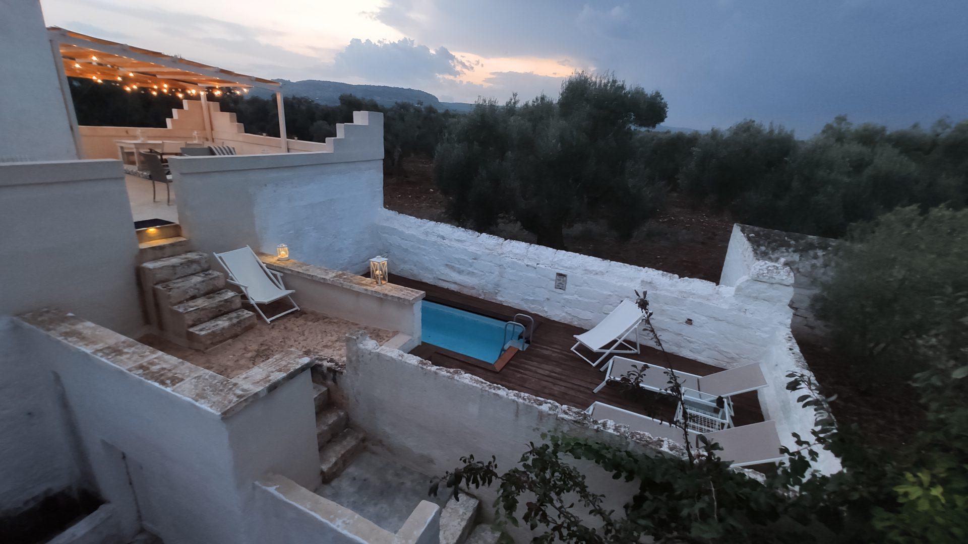 Panorama of Swimming pool deck, walls and olive groves at Pool at Masseria Bellavista historic holiday vacation rental villa in ostuni puglia seaview at dusk