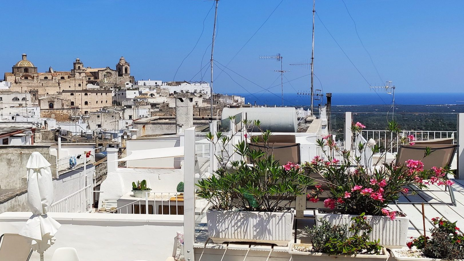 Amazing panorama of Puglia's Ostuni Old Town and the blue Adriatic sea from the upper rooftop terrace at Casa dei Fiori holiday rental home